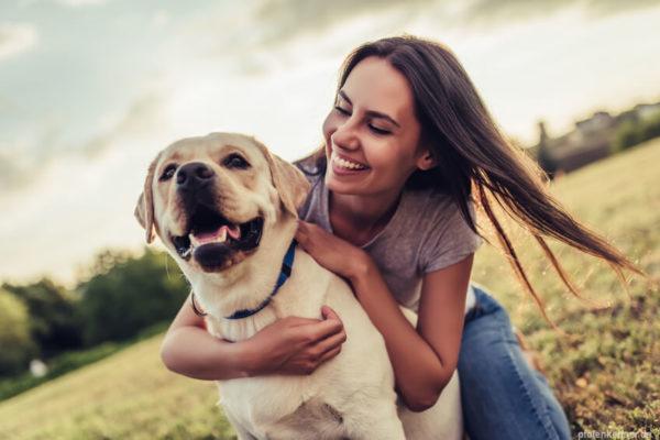 Lächelnde Frau, welche einen Hund umarmt